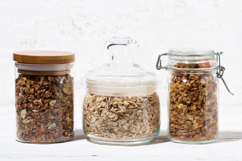 有燕麦剥落和格兰诺拉麦片的玻璃瓶子 免版税库存照片