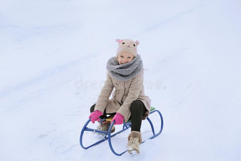 有爬犁的女孩获得乐趣在雪在度假寒假 免版税库存照片