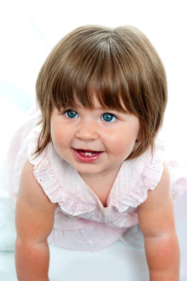 有爬行在地面上的乳齿的女婴 免版税库存图片