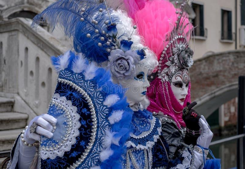 有爱好者、佩带的手画面具和华丽蓝色和桃红色服装的两名妇女在威尼斯狂欢节 免版税库存图片