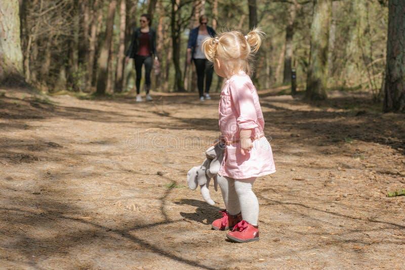 有爱拥抱玩具的孩子在有她的父母的森林里走 库存照片