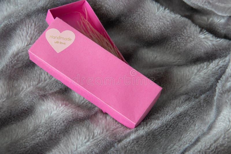 有爱的心脏的大桃红色礼物盒在银灰色蓬松虚假毛皮一揽子背景的 免版税库存图片