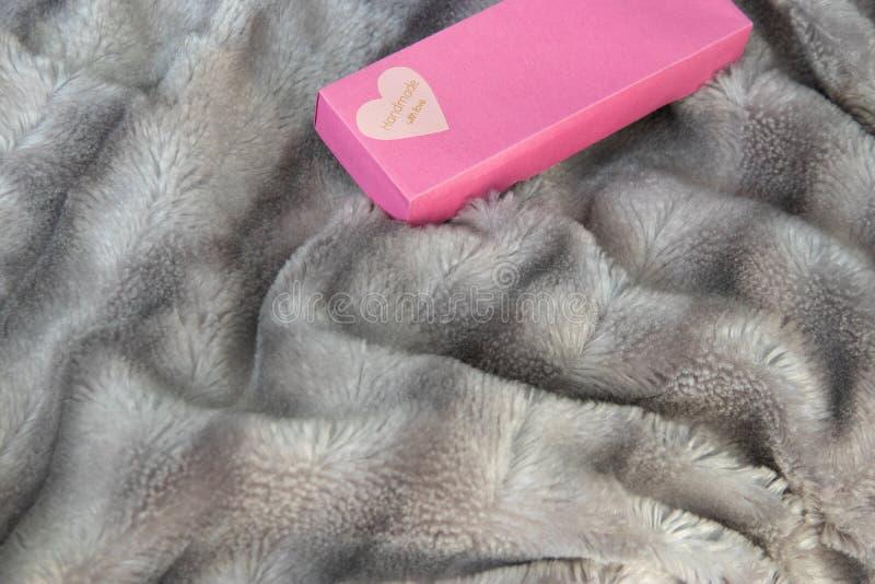 有爱的心脏的大桃红色礼物盒在银灰色蓬松虚假毛皮一揽子背景的 免版税图库摄影
