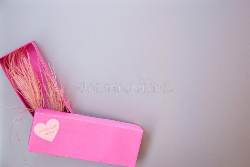有爱的心脏的大桃红色礼物盒在银灰色金属背景的 库存照片