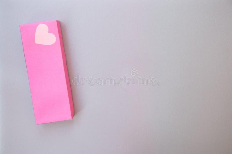 有爱的心脏的大桃红色礼物盒在银灰色金属背景的 免版税库存照片