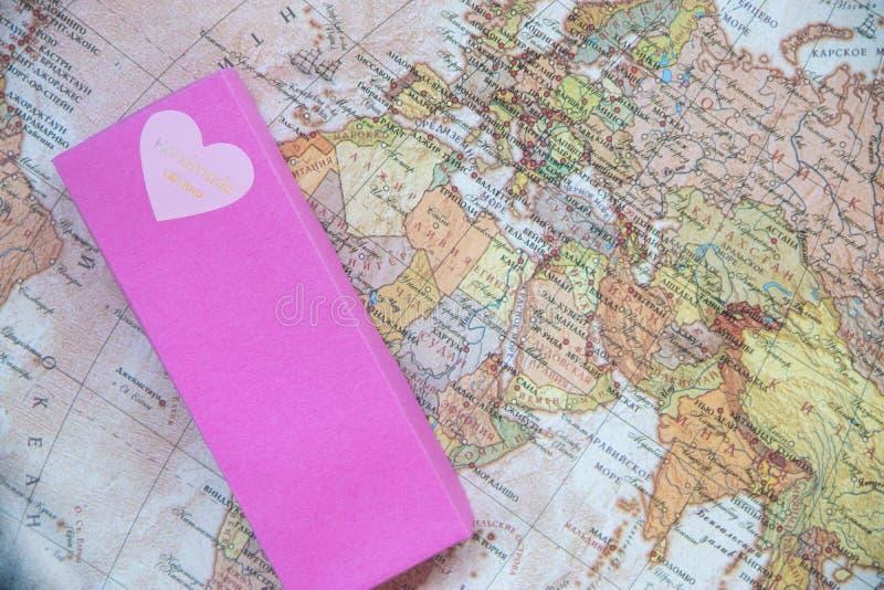 有爱的心脏的桃红色箱子在世界地图的 库存图片