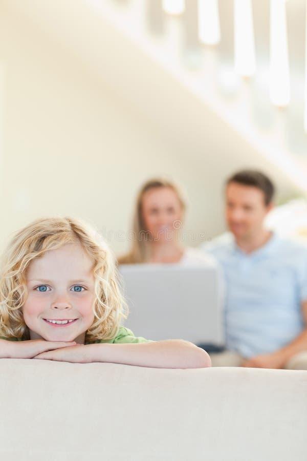 有父母的愉快的男孩在背景中 免版税库存照片