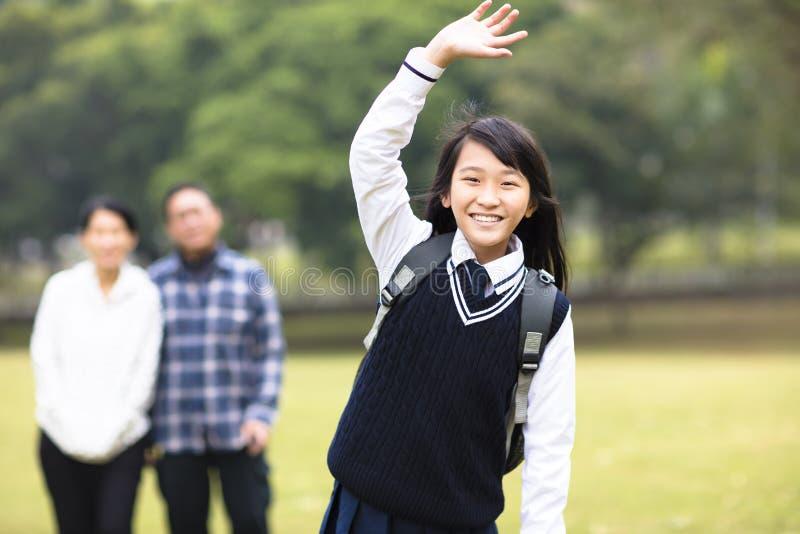 有父母的年轻学生女孩在学校 库存照片