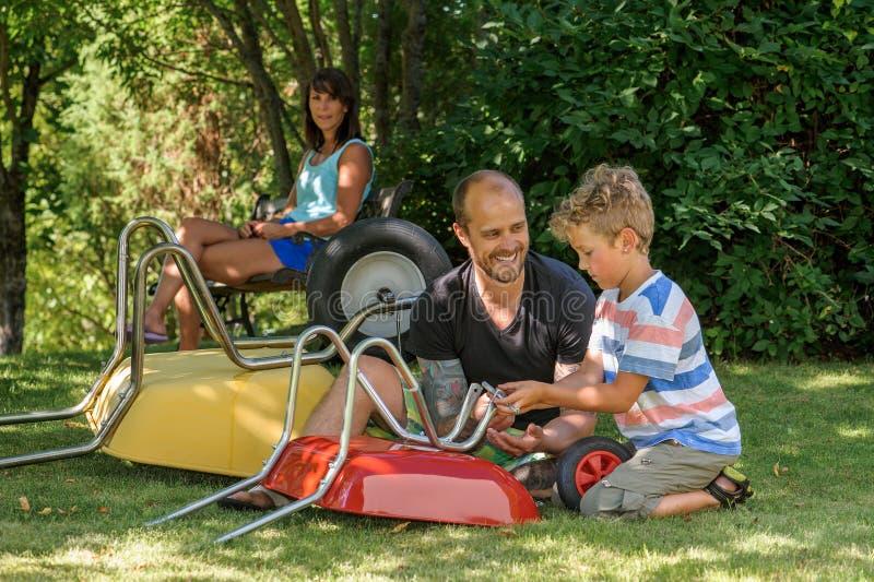 有爸爸和独轮车的男孩 免版税库存照片