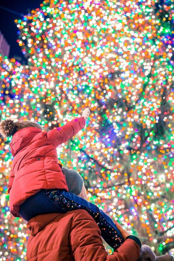 有爸爸的愉快的女孩洛克菲勒圣诞树的背景的在纽约 库存图片