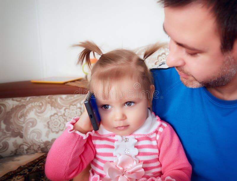 有爸爸的婴孩收到在祖父母的电话 免版税库存图片