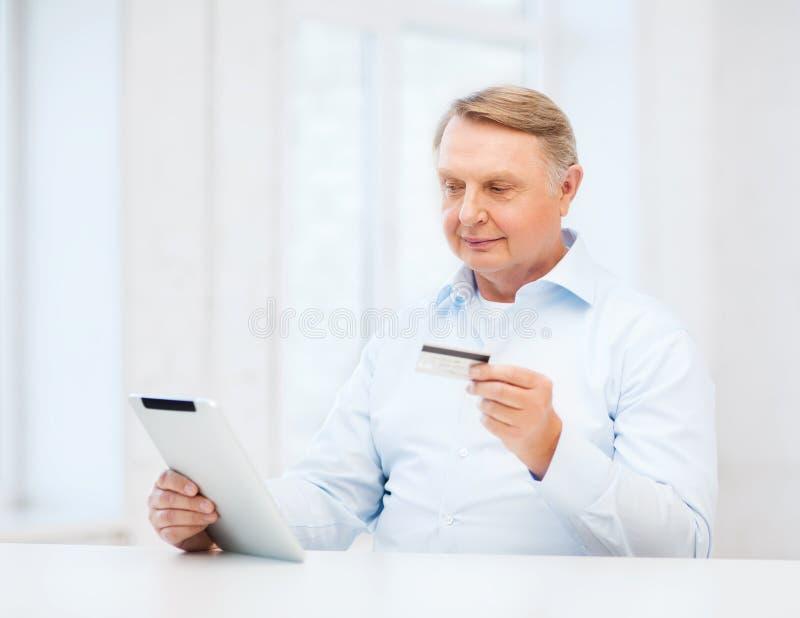 有片剂个人计算机和信用卡的老人在家 图库摄影