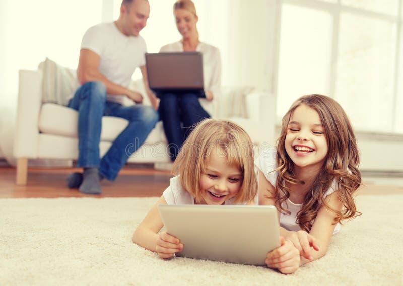 有片剂个人计算机和父母的微笑的姐妹  免版税库存照片