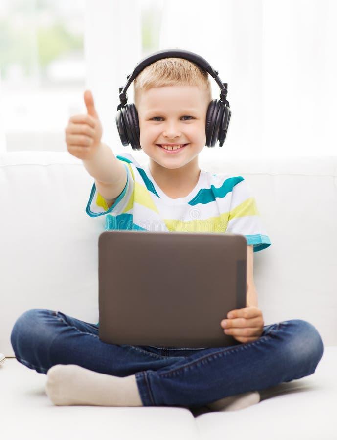 有片剂个人计算机和耳机的小男孩在家 库存图片