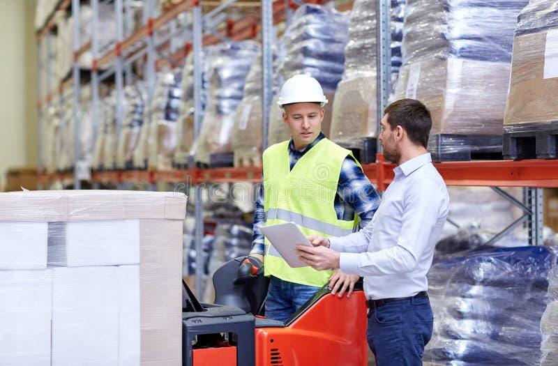 有片剂个人计算机和铲车的人在仓库 免版税图库摄影