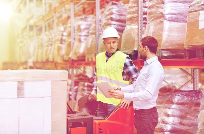 有片剂个人计算机和铲车的人在仓库 免版税库存照片