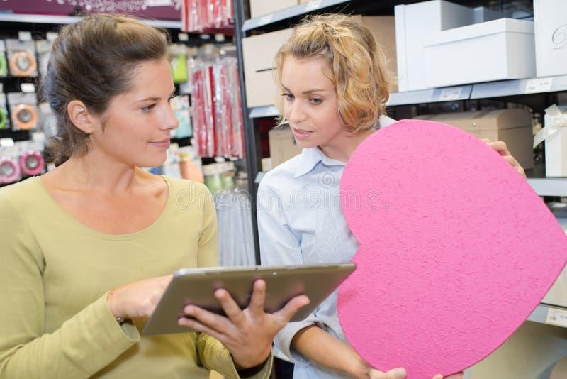 有片剂个人计算机帮助的妇女的愉快的售货员 免版税库存照片