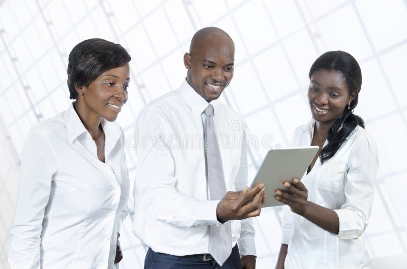 有片剂个人计算机的三个非洲商人 免版税库存图片