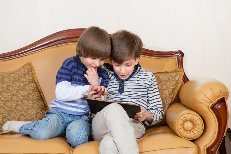 有片剂个人计算机的两个男孩 库存图片