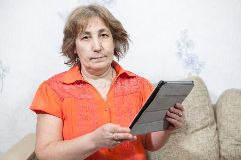 有片剂个人计算机的中年白种人妇女坐的沙发在手上 免版税库存图片