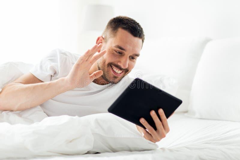 有片剂个人计算机的人有录影电话在床 图库摄影