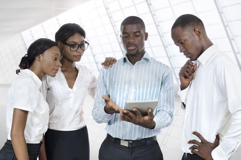 有片剂个人计算机的四个非洲商人 免版税库存图片