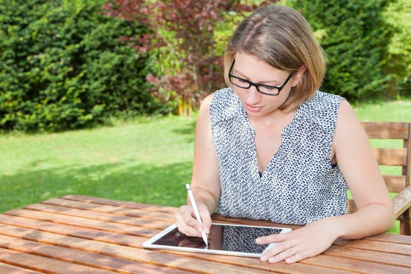有片剂个人计算机的妇女在庭院里 免版税库存照片