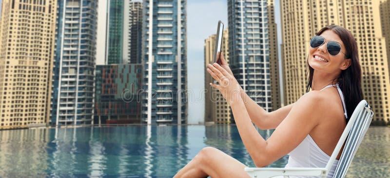 有片剂个人计算机的妇女晒日光浴在城市水池的 库存照片