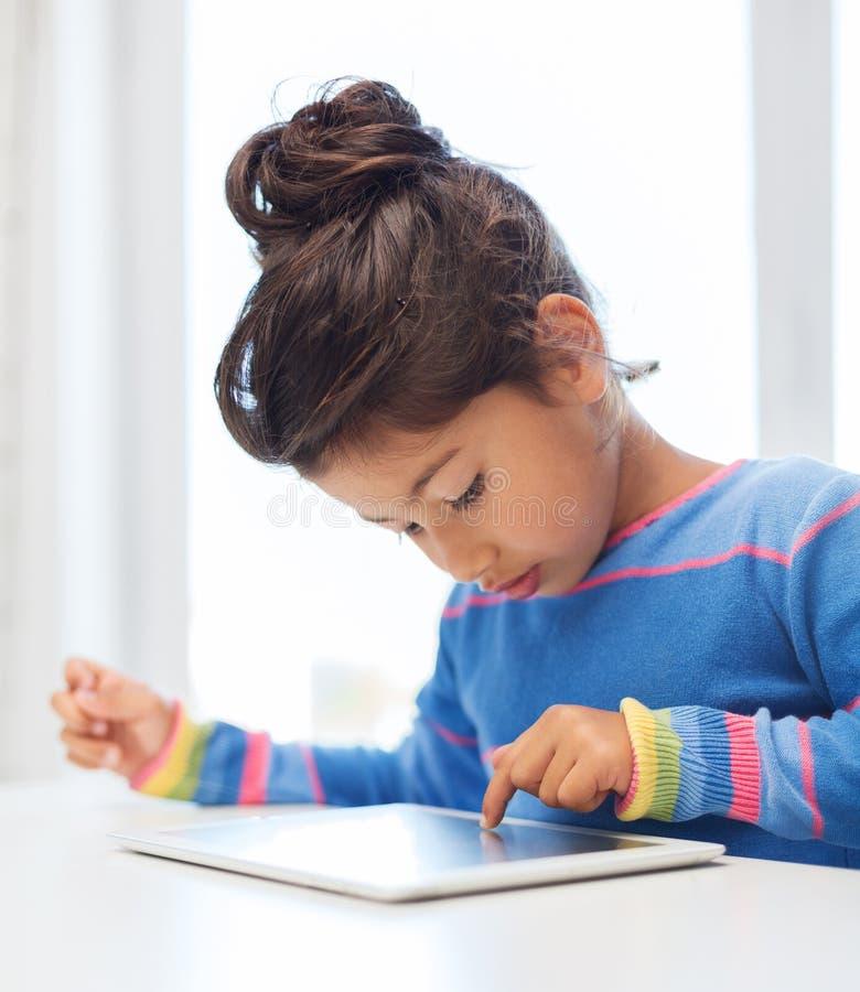 有片剂个人计算机的小女孩 免版税库存图片