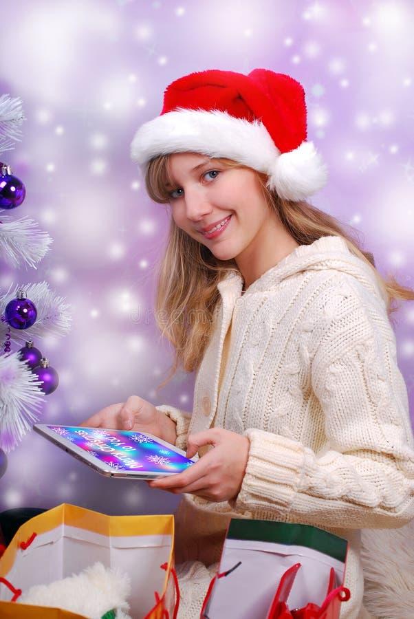 有片剂个人计算机的愉快的女孩作为完善的圣诞节礼物 免版税库存照片