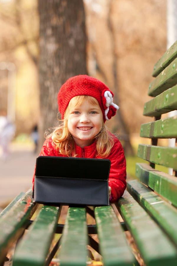 有片剂个人计算机的愉快的小女孩在长凳 库存照片
