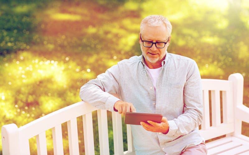 有片剂个人计算机的老人在夏天公园 免版税库存图片