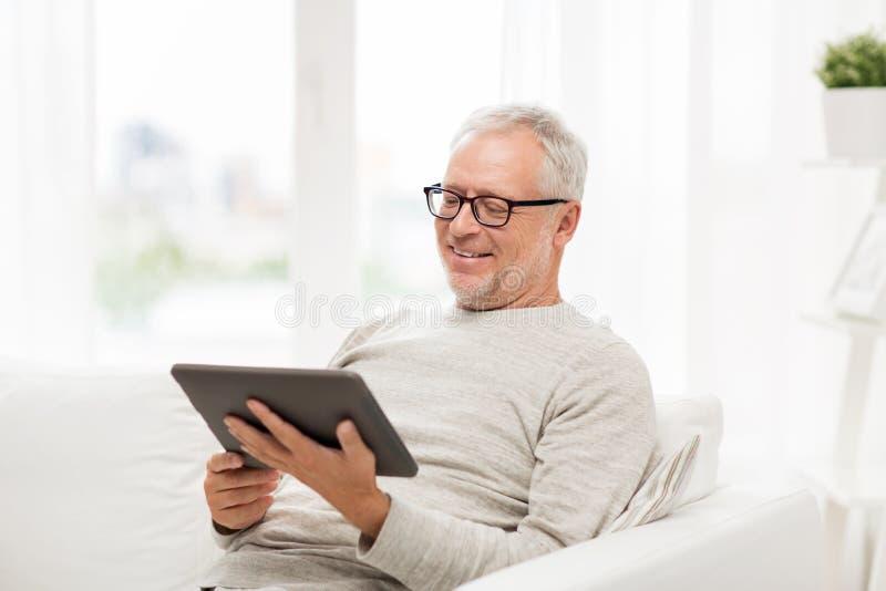 有片剂个人计算机的老人在家 免版税库存图片