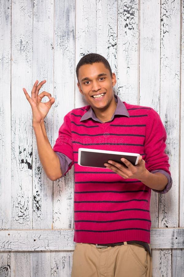 有片剂个人计算机的英俊的年轻人在演播室 免版税库存图片