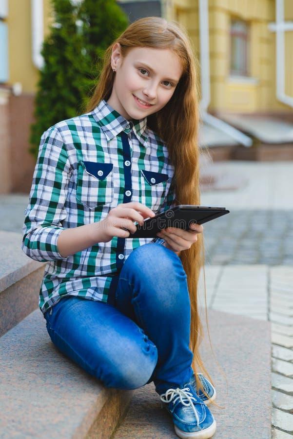 有片剂个人计算机计算机的微笑的十几岁的女孩户外 免版税图库摄影