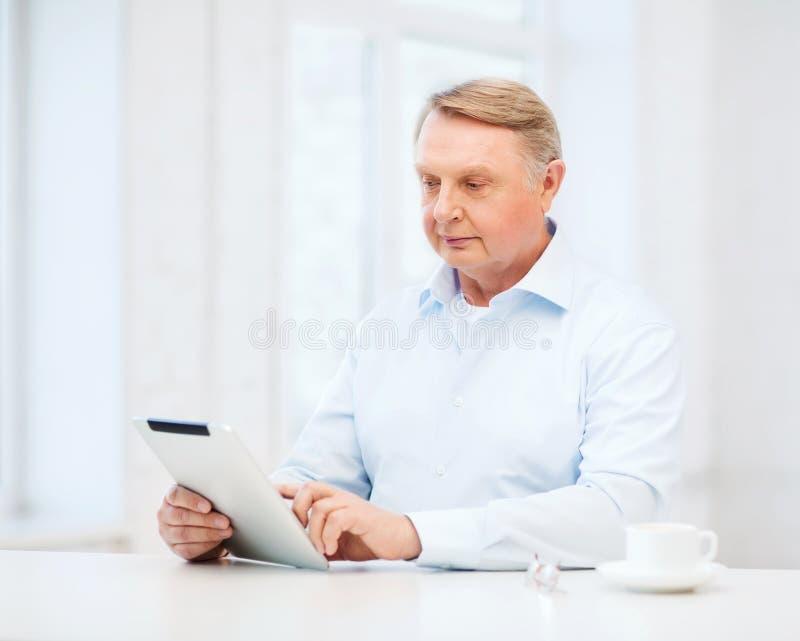 有片剂个人计算机计算机的老人在家 库存照片