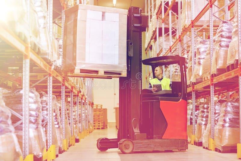 有片剂个人计算机运行的铲车的人在仓库 免版税库存图片