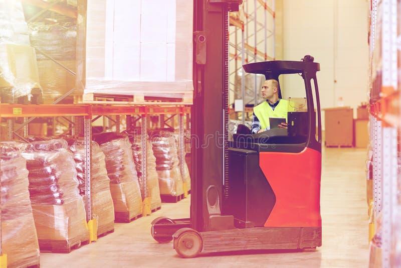 有片剂个人计算机运行的铲车的人在仓库 库存图片