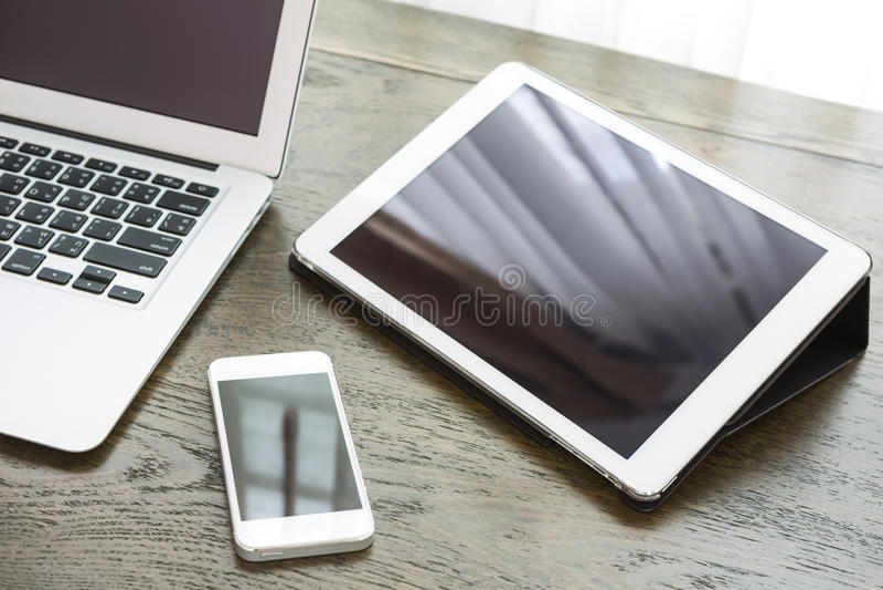 有片剂和巧妙的电话的膝上型计算机在桌上 免版税库存照片