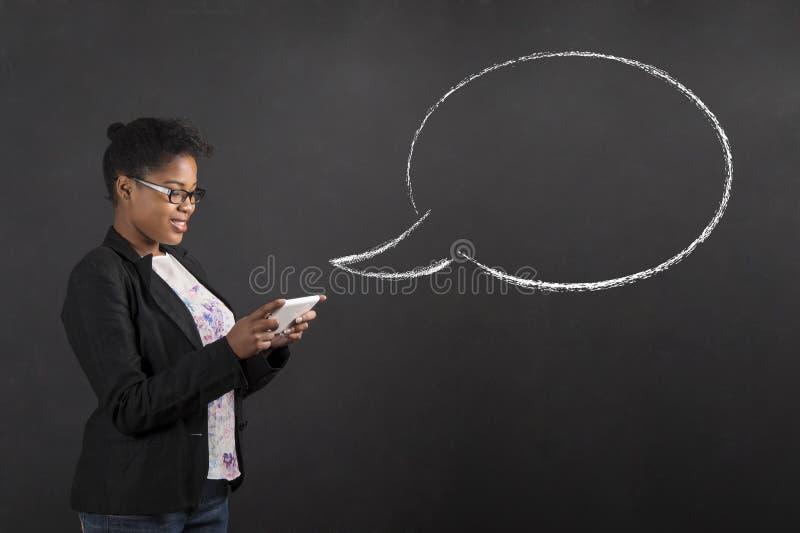 有片剂和讲话或者想法泡影的非洲妇女在黑板背景 库存图片
