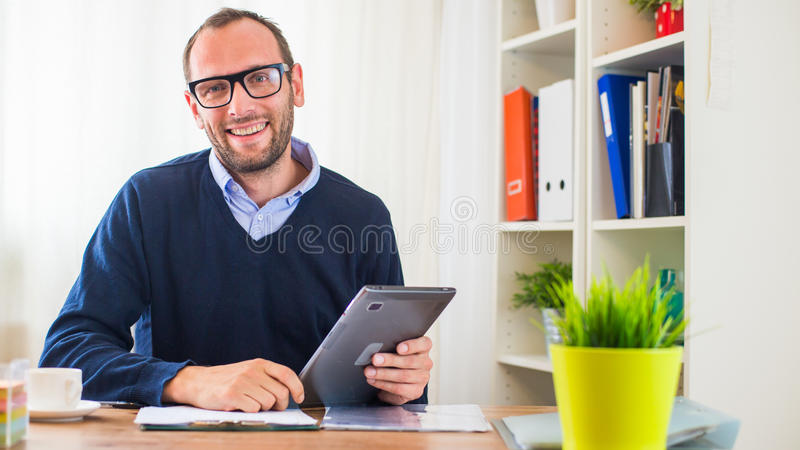 有片剂的一个年轻白种人人在他的办公室。 免版税库存照片