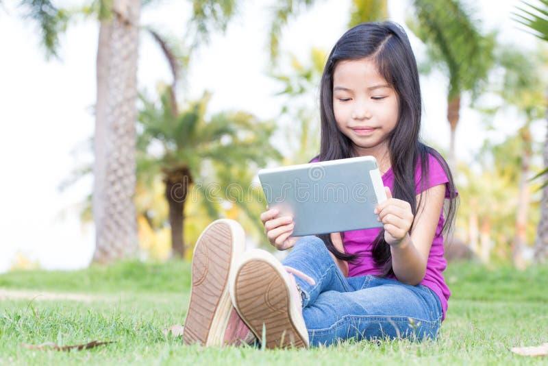 有片剂的亚裔小女孩 库存图片