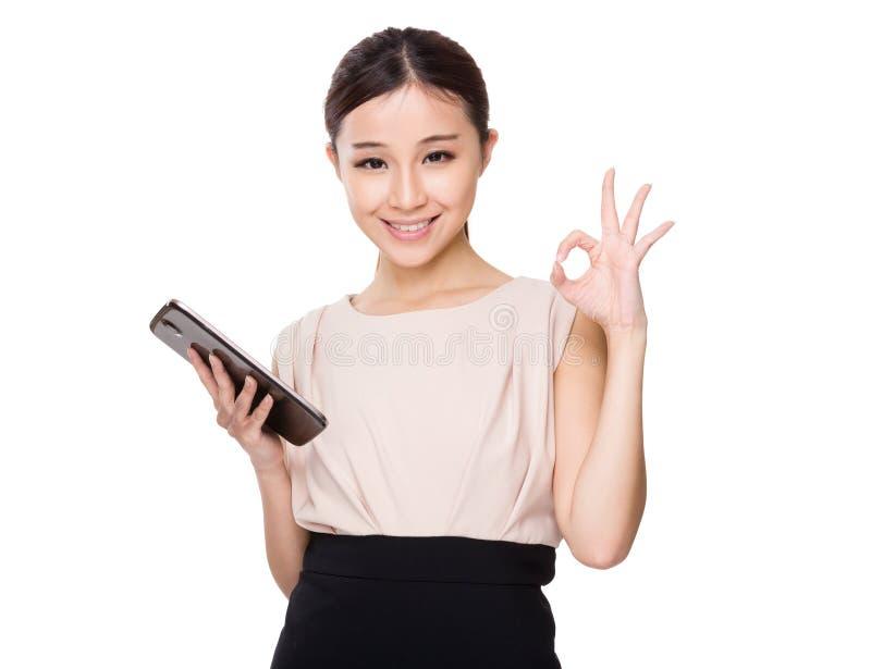 有片剂的亚洲妇女举行和好标志打手势 免版税库存图片