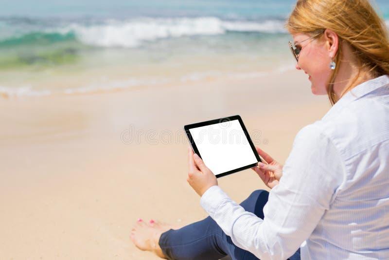 有片剂的企业人在海滩 免版税库存图片