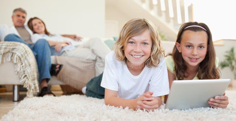 有片剂的兄弟姐妹在地毯 免版税库存图片