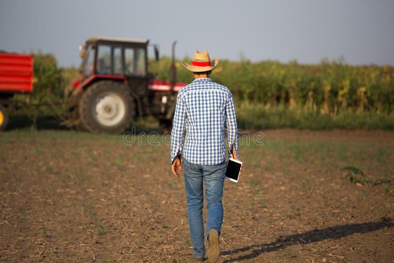有片剂的农夫在拖拉机前面 库存照片