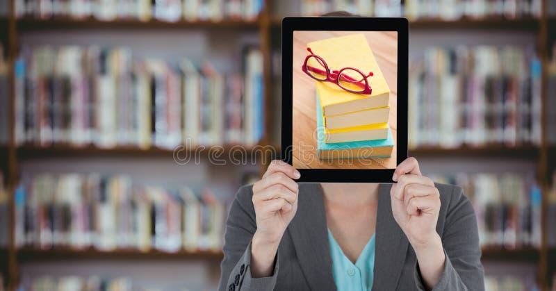 有片剂的女商人在她的与堆的面孔书,当站立在图书馆时 免版税库存照片