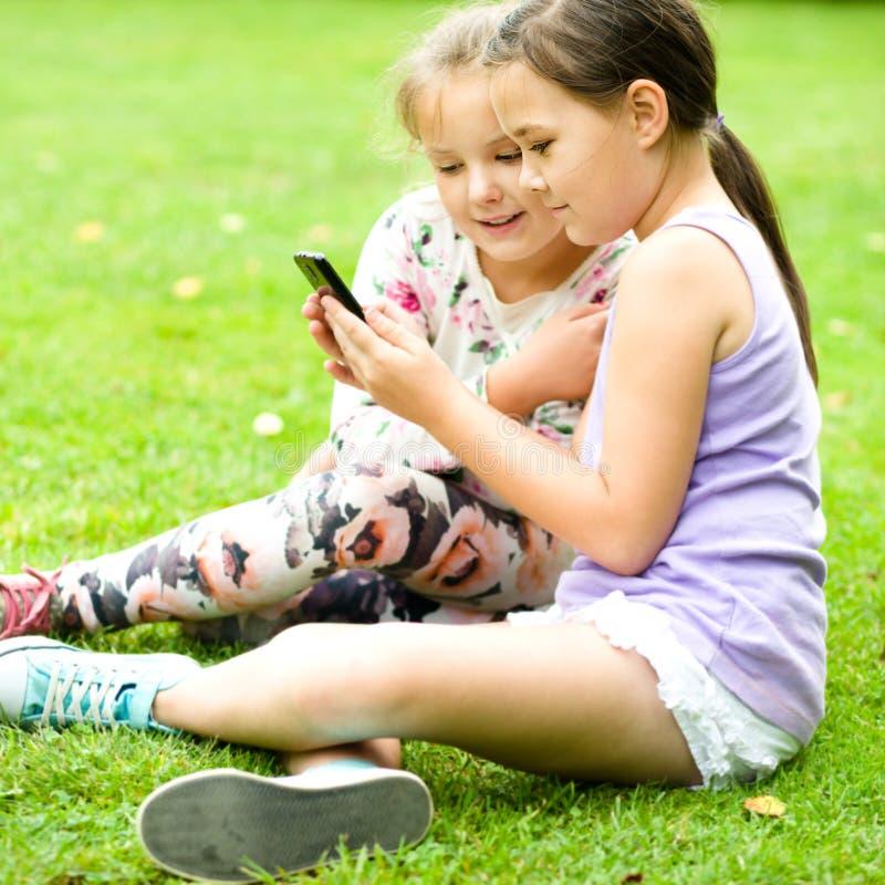 有片剂的女孩在公园 免版税库存图片