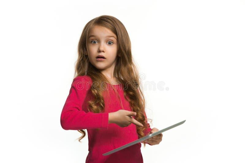 有片剂的小滑稽的女孩在白色背景 库存图片