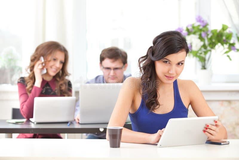 有片剂的微笑的女孩在咖啡馆 免版税库存照片